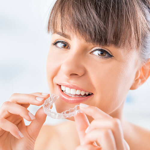 A woman holding an Invisalign clear aligner in Bloomfield Hills