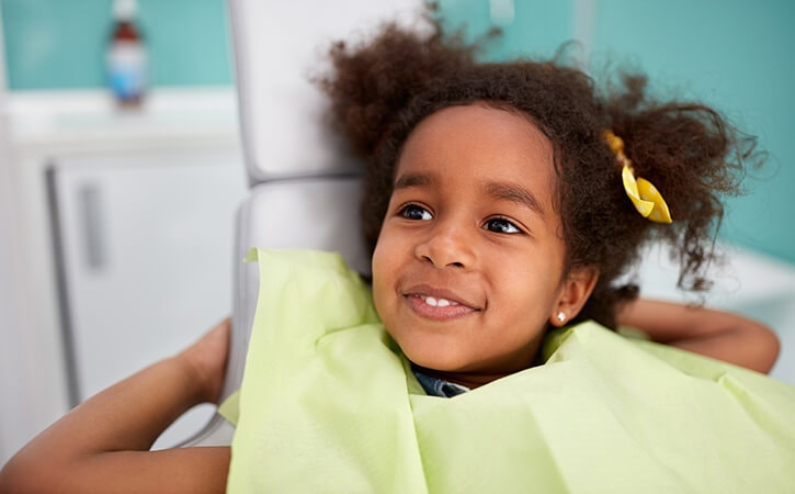 A little girl sitting in the chair at our dentists in Bloomfield Hills, MI while smiling and wearing a green dentist bib