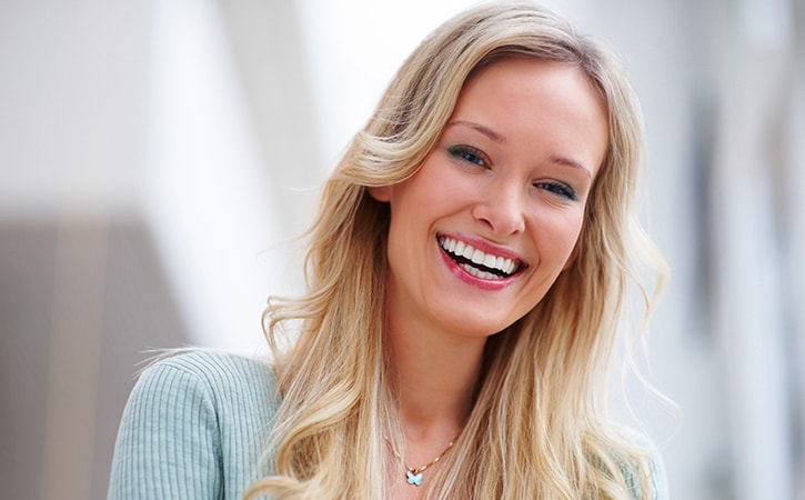 A blonde woman with perfect teeth smiling after her Dillingham Hanson visit