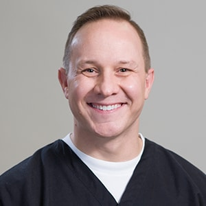 One of our dentists in Bloomfield Hills, MI smiling while wearing his black dentist uniform