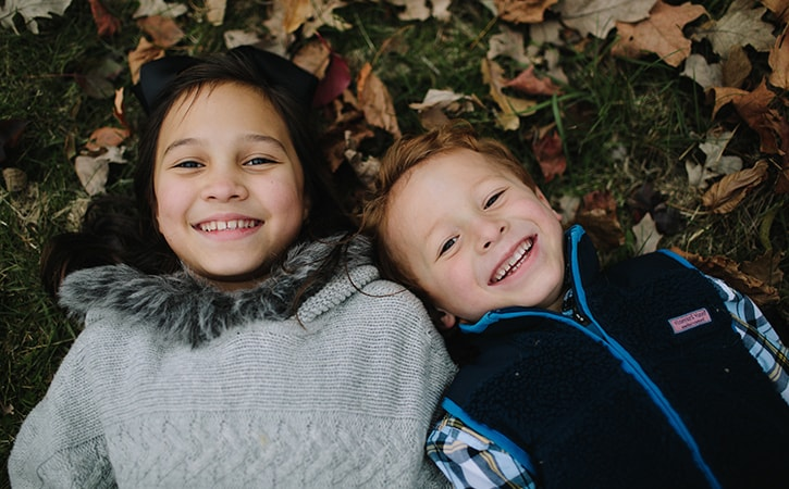 Two little boys lying on the grass and dry leaves while smiling and wearing sweaters