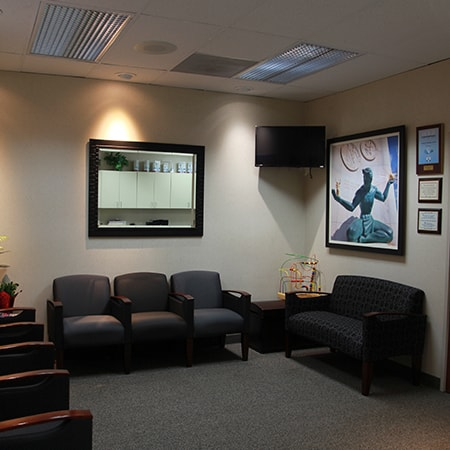 The waiting room of our dental office showing the chairs, tables, and a TV screen