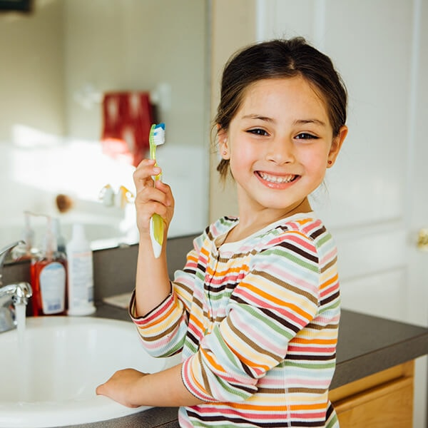 A little girl in front of a mirror brushing her teeth before her family dentistry appointment