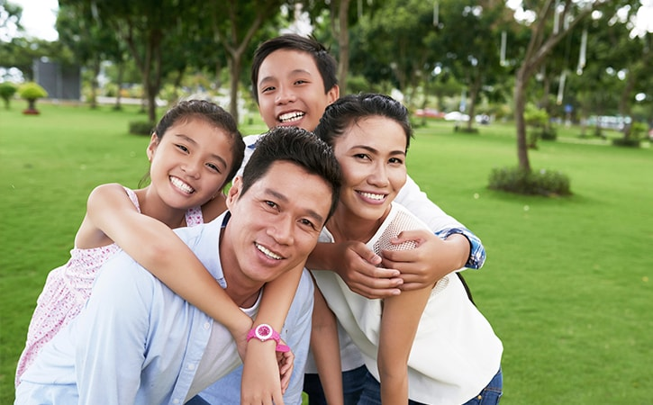A family of four in a park smiling as they hug