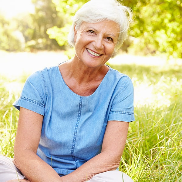 An older woman smiling after getting new dental implants