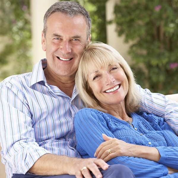 An older couple holding each other after getting dental implants in Bloomfield Hills