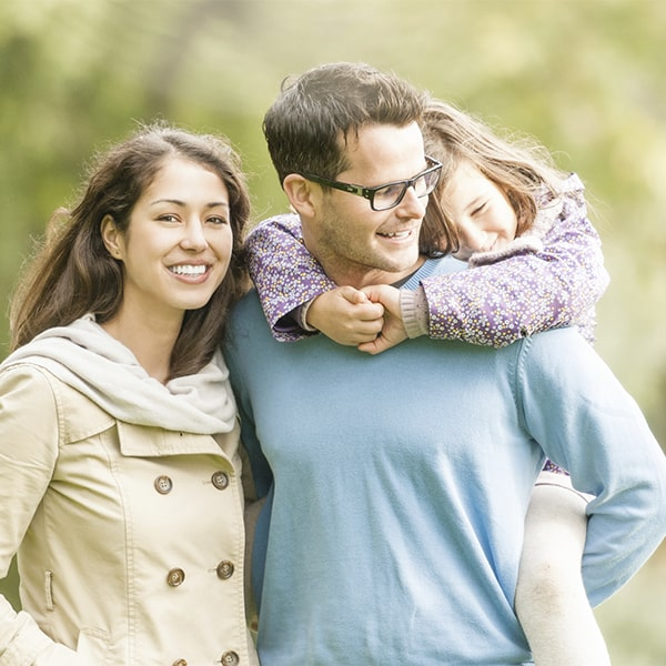 A family of three walking with mother smiling with porcelain veneers in Bloomfield Hills