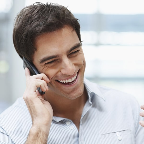 A man on phone with porcelain veneers from Dillingham Hanson