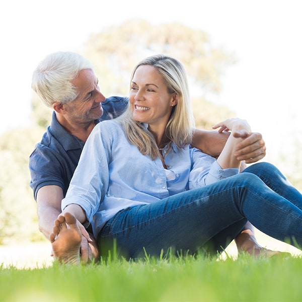 Older couple sitting on grass after a root canal at Dillingham Hanson